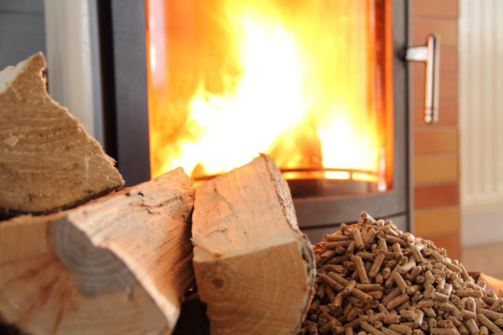 pellets and logs in front of a lit wood stove