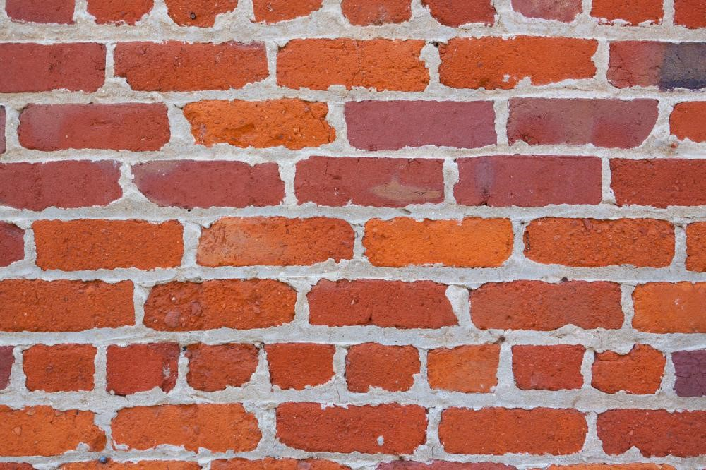 A brick wall with freshly applied mortar