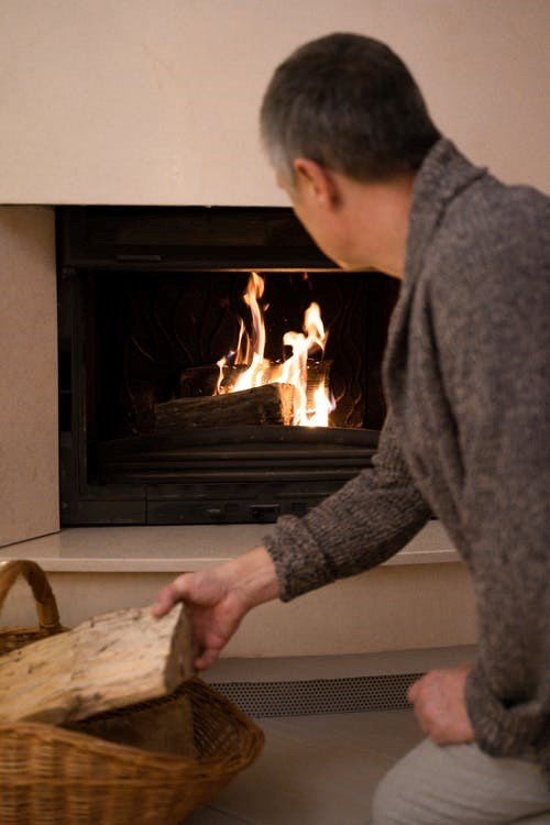 man adding more wood to the fireplace