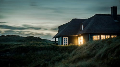 a lit-up home with a chimney in the fields at dusk